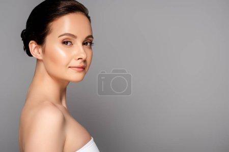 Photo pour Vue latérale de belle femme avec une peau parfaite regardant la caméra isolée sur gris - image libre de droit