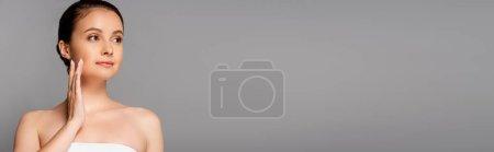 Photo pour Belle femme avec une peau parfaite touchant le visage et regardant loin isolé sur gris, vue panoramique - image libre de droit
