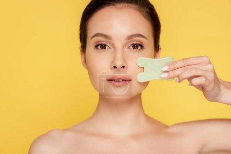Photo pour Belle femme nue faciale jade gua sha isolé sur jaune - image libre de droit