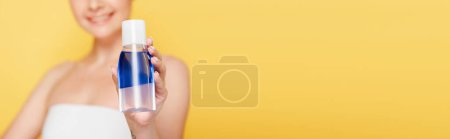 Photo for Selective focus of smiling beautiful woman holding micellar water in bottle isolated on yellow, panoramic shot - Royalty Free Image