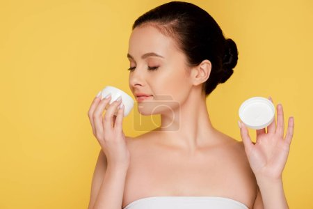 beautiful woman smelling cosmetic cream isolated on yellow