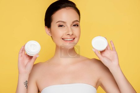 Photo for Smiling beautiful woman holding container with cosmetic cream isolated on yellow - Royalty Free Image