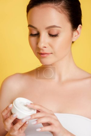 Photo for Beautiful woman holding container with cosmetic cream isolated on yellow - Royalty Free Image