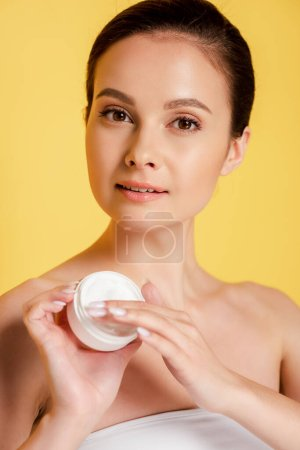 beautiful woman applying cosmetic cream on fingers isolated on yellow