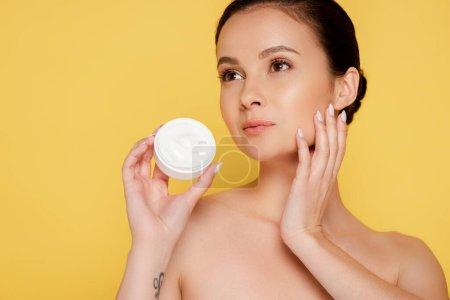 Photo pour Belle femme nue tenant récipient avec crème cosmétique isolé sur jaune - image libre de droit
