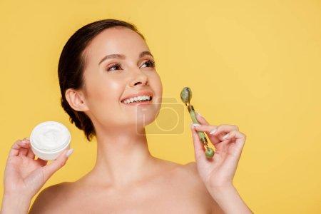 lächelnd nackt schöne Frau hält kosmetische Creme und Jade-Rolle isoliert auf gelb