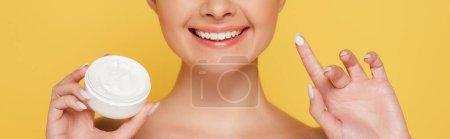 Photo pour Vue recadrée de sourire nue belle femme avec crème cosmétique sur le doigt isolé sur jaune, vue panoramique - image libre de droit