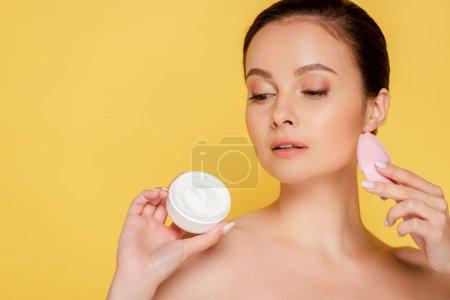 hermosa mujer desnuda sosteniendo crema cosmética y cepillo de limpieza facial aislado en amarillo