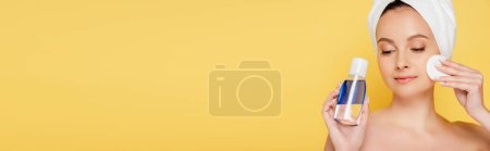 Photo for Beautiful naked woman with towel on head, micellar water and cotton pad isolated on yellow, panoramic shot - Royalty Free Image