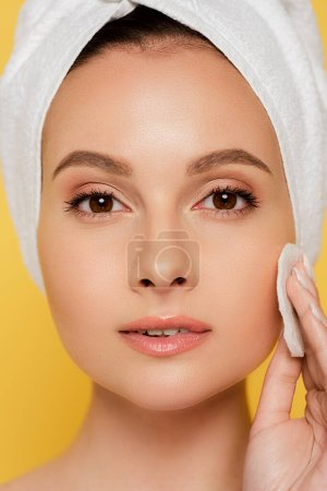 beautiful woman with towel on head using cotton pad isolated on yellow