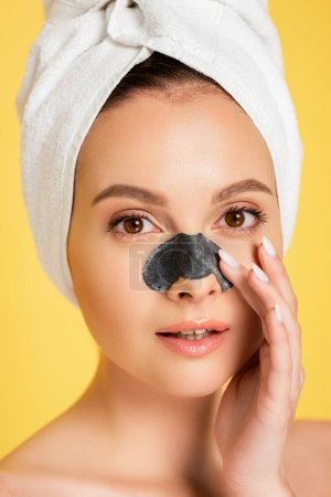 beautiful naked woman with towel on head and blackhead remover on  nose isolated on yellow
