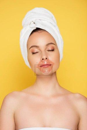 schöne Frau mit Handtuch auf dem Kopf, Lippenstift und geschlossenen Augen isoliert auf gelb