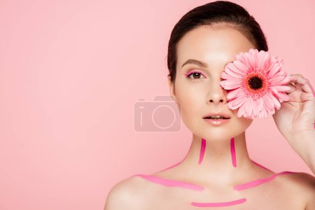 naked beautiful woman with pink lines on body and chrysanthemum near eye isolated on pink