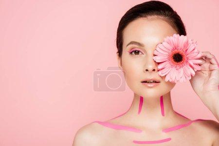 nackte schöne Frau mit rosa Linien auf dem Körper und Chrysanthemen in Augennähe isoliert auf rosa