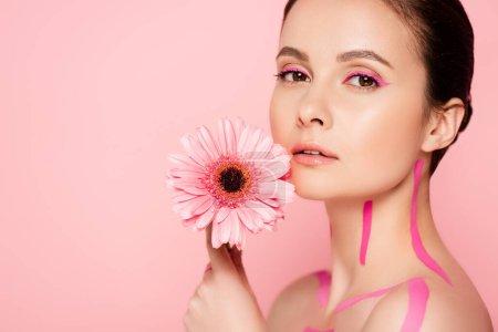 hermosa mujer desnuda con líneas de color rosa en el cuerpo y crisantemo aislado en rosa