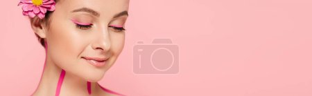 smiling beautiful woman with pink lines on body and flower isolated on pink, panoramic shot