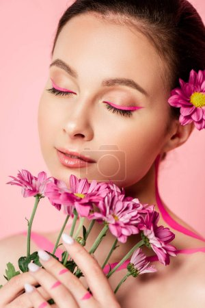 naked beautiful woman with closed eyes, pink lines on body and flower in hair holding bouquet isolated on pink