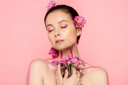 Photo for Naked beautiful woman with closed eyes, pink lines on body and flowers in hair holding bouquet isolated on pink - Royalty Free Image