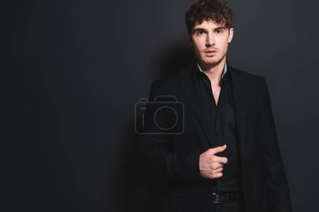 handsome man in formal wear touching blazer and looking at camera on black