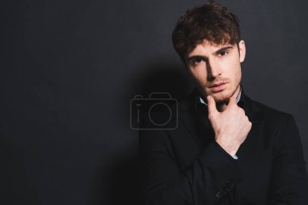 Photo for Handsome man in formal wear looking at camera and touching face on black - Royalty Free Image