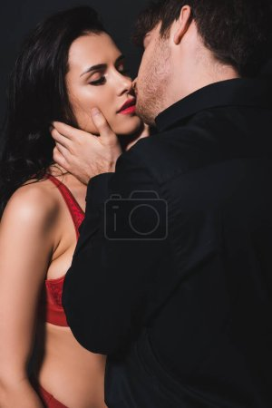 Photo for Man kissing attractive woman with closed eyes isolated on black - Royalty Free Image