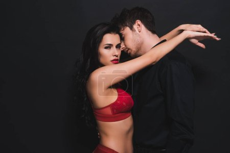 Photo for Sexy woman in red bra and panties hugging handsome man isolated on black - Royalty Free Image