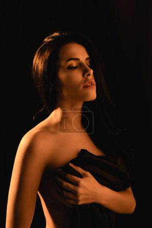 Photo pour Éclairage sur femme sensuelle avec les yeux fermés enveloppé dans drap de lit en soie isolé sur noir - image libre de droit