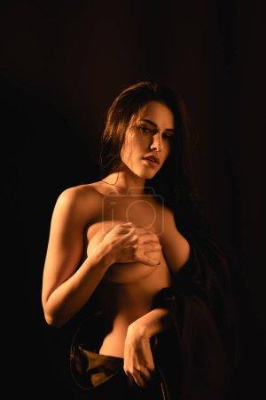 Photo pour Femme sexy enveloppé dans drap de lit en soie couvrant poitrine isolé sur noir - image libre de droit