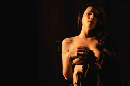Photo for Lighting on beautiful woman wrapped in silk bed sheet covering breast isolated on black - Royalty Free Image