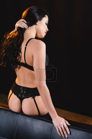 Photo for Sexy woman in lace underwear sitting on sofa and touching hair on black - Royalty Free Image