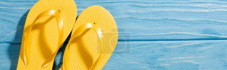 Photo for Top view of yellow flip flops on wooden blue background, panoramic shot - Royalty Free Image
