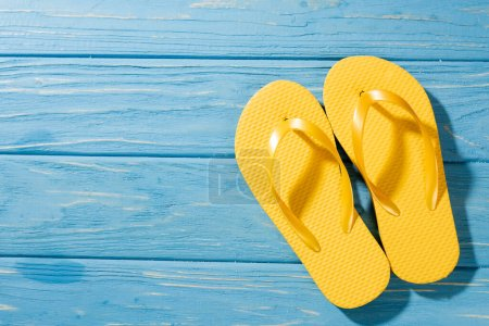 Photo for Top view of yellow flip flops on wooden blue background - Royalty Free Image