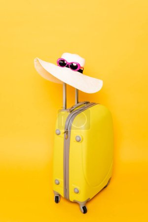 Photo pour Chapeau de soleil et lunettes de soleil sur la valise poignée sur fond jaune - image libre de droit