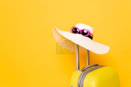 Photo for Sun hat and sunglasses on suitcase handle on yellow background - Royalty Free Image