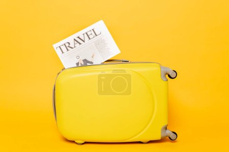 Photo for Travel newspaper on colorful suitcase on yellow background - Royalty Free Image