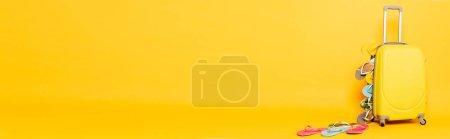 Photo pour Sac de voyage avec des tongs colorées sur fond jaune, vue panoramique - image libre de droit