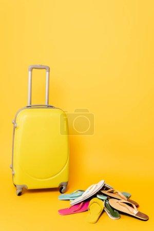 Photo pour Sac de voyage avec des tongs colorées sur fond jaune - image libre de droit