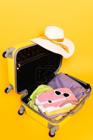 Photo for Open travel bag with summer clothes and accessories on yellow background - Royalty Free Image