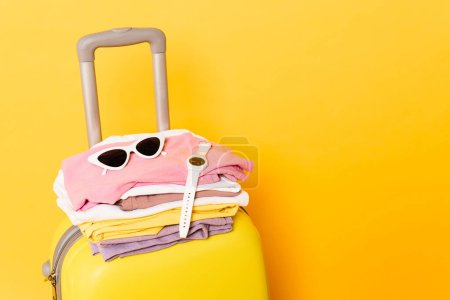 travel bag with summer clothes and accessories on yellow background