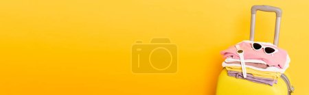 Photo for Travel bag with summer clothes and accessories isolated on yellow, panoramic shot - Royalty Free Image