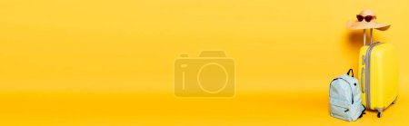 Photo for Travel bag with sun hat and sunglasses near backpack on yellow background, panoramic shot - Royalty Free Image