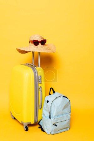 Photo pour Sac de voyage avec chapeau de soleil et lunettes de soleil près du sac à dos sur fond jaune - image libre de droit