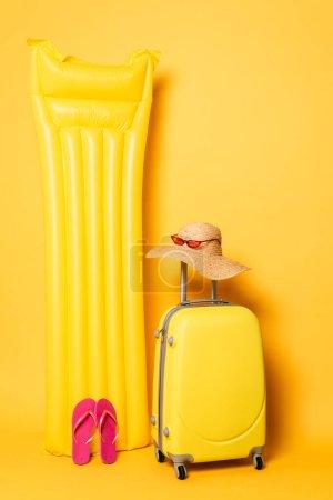 Photo pour Sac de voyage près de la piscine flotteur avec accessoires de plage sur fond jaune - image libre de droit