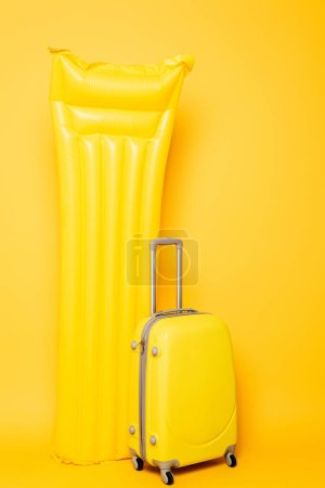 Photo for Travel bag near pool float on yellow background - Royalty Free Image