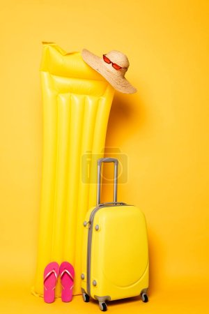 Photo for Travel bag near pool float with beach accessories on yellow background - Royalty Free Image