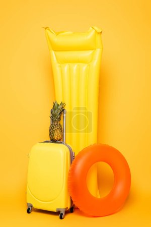 Photo for Travel bag with pineapple near pool floats on yellow background - Royalty Free Image