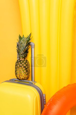 Photo pour Vue rapprochée du sac de voyage avec ananas près des flotteurs de piscine sur fond jaune - image libre de droit