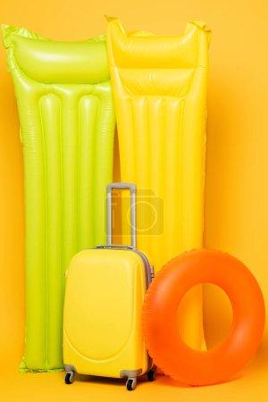 Photo pour Sac de voyage avec flotteurs de piscine sur fond jaune - image libre de droit