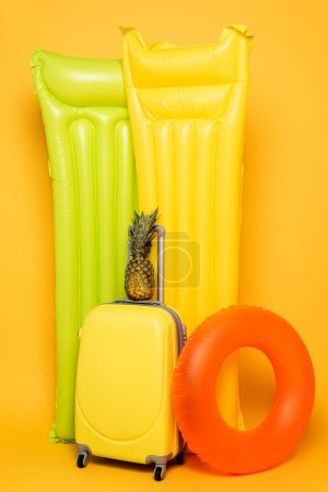 travel bag with pineapple near pool floats on yellow background