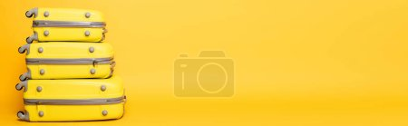 Photo for Stack of travel bags on yellow background, panoramic shot - Royalty Free Image